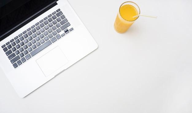 さわやかなオレンジジュースとラップトップ
