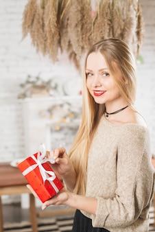 ロマンチックなプレゼントを保持している美しい女性