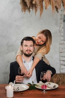 テーブルで美しい抱きしめるカップル
