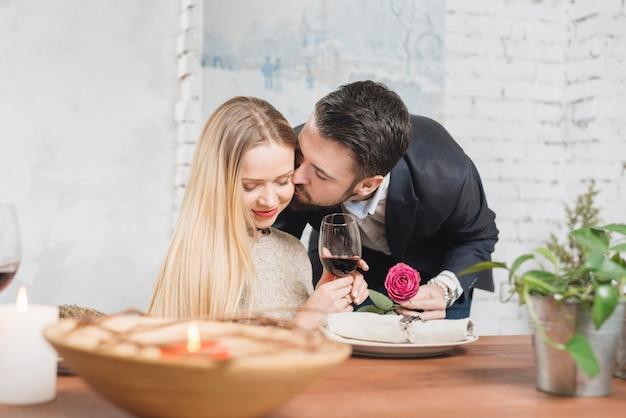バラを与えると頬にキスをする女性