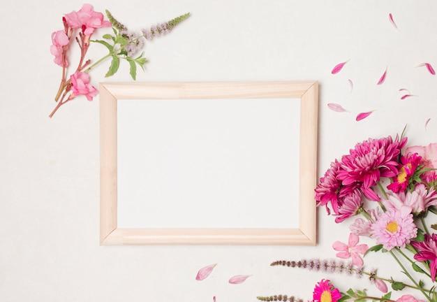素敵なピンクの花の構図の間のフォトフレーム