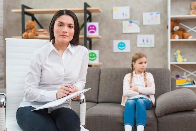 クリップボードと落ち込んでいる女の子の前に座っているペンで椅子に座っている若い女性心理学者