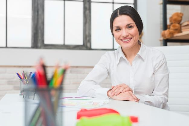 Улыбается портрет молодой уверенно женского психолога, сидя в своем кабинете
