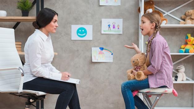 彼女と話している女性の心理学者の前に座って意気消沈した少女