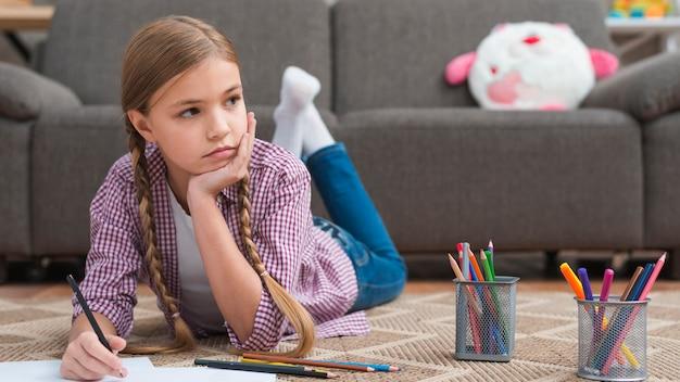 色鉛筆で描くカーペットの上に横たわる落ち込んでいる女の子