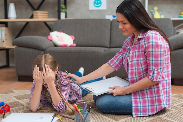 泣いている少女を慰める女性心理学者
