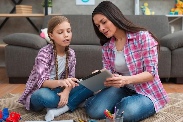 カーペットの上に座っている女の子に女性の心理学者示すデジタルタブレット