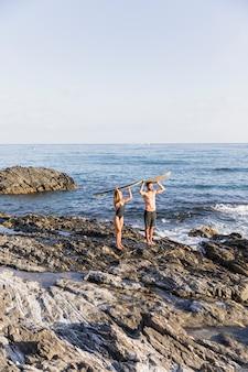 サーフボードを頭の上に保つ若いカップル