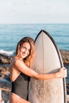 Улыбающаяся женщина позирует с доской для серфинга