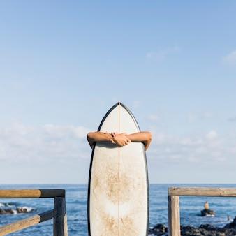Неузнаваемый человек обнимает доску для серфинга у моря