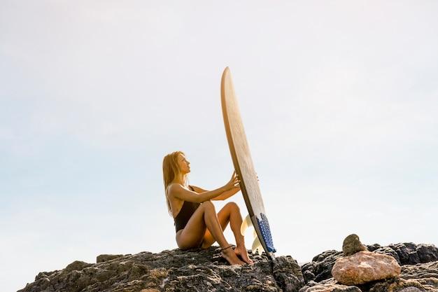 Женщина сидит на берегу моря с доской для серфинга