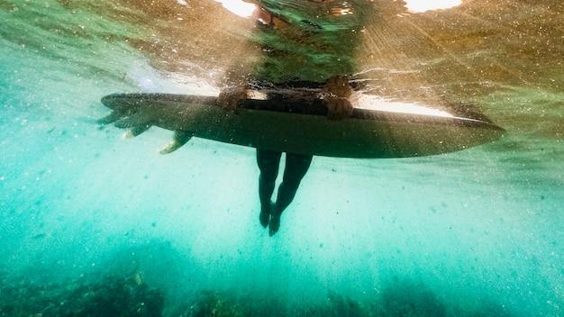 青い海の水でサーフボードに横になっている人