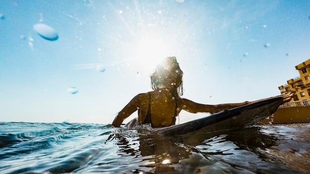 青い水のサーフボードで泳いでいる若い女性