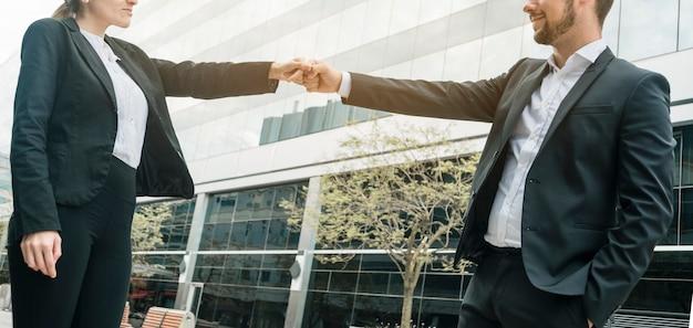 ビジネスマンや建物のバンピング拳の前に立っている女性実業家のクローズアップ