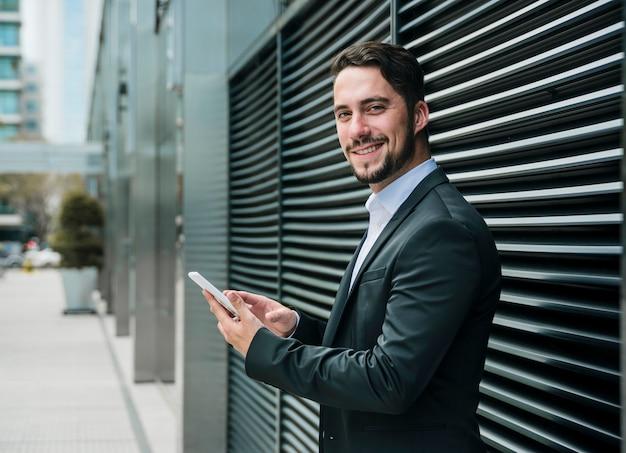 手で携帯電話を保持している事務所ビルの外に立っている笑顔の青年実業家