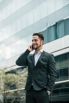 ポケットに手を携帯電話で話している青年実業家