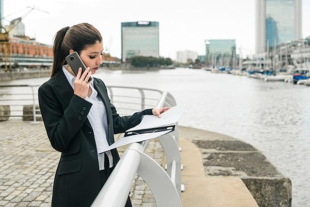 Молодая коммерсантка стоя на гавани говоря на мобильном телефоне пока смотрящ доску сзажимом для бумаги