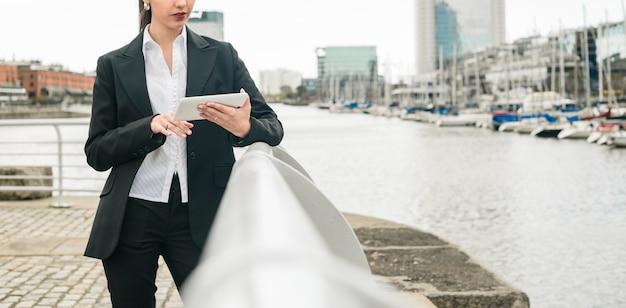 Крупный план молодой предприниматель, опираясь на перила возле гавани, с помощью мобильного телефона