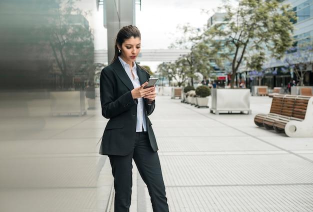 携帯電話を使用してビジネスキャンパスに立っている若い実業家