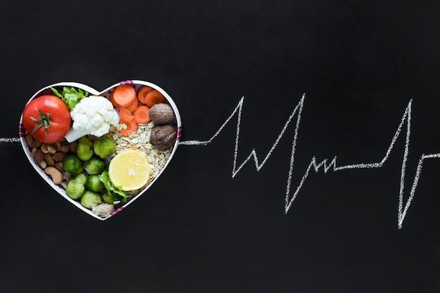 黒の背景に心電図ライフラインとしてハート形に配置された野菜と健康的な生活のコンセプト