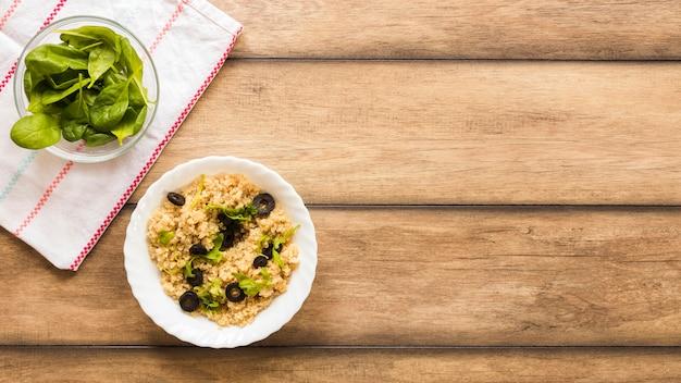 バジルの葉とオリーブの朝食を添えて健康的なオート麦のボウル