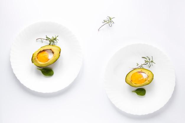 Авокадо запеченный с яйцом в тарелке на белом фоне