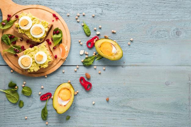 まな板の上のゆで卵とトーストのパンとアボカドで焼き有機卵