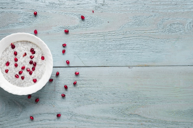 木製のテーブルの上の白いボウルにチアシードプリンの立面図