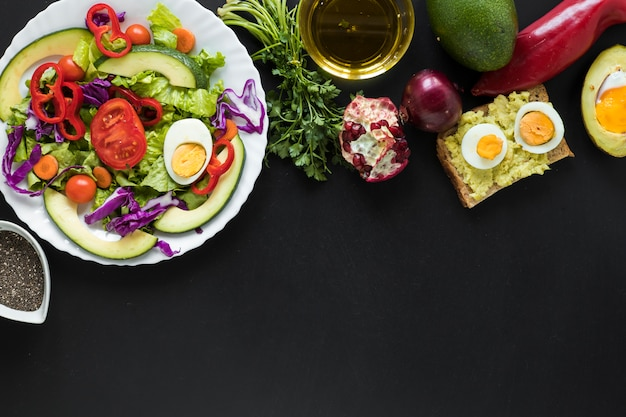新鮮野菜のサラダ。焼いたパンフルーツ黒の背景上のオイル