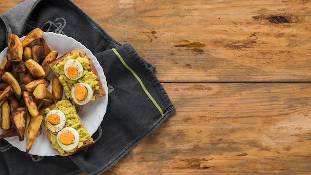 Ломтик поджаренного хлеба с вареными яйцами и кусочки жареного хлеба в тарелке