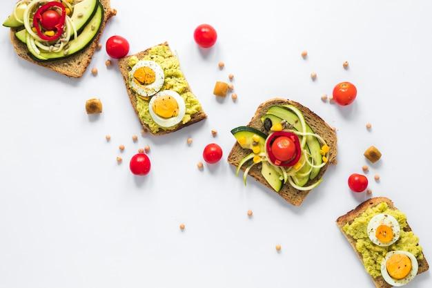 Вид сверху здоровый бутерброд с вареным яйцом и нарезанным авокадо