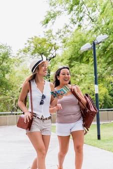 Две улыбающиеся молодые женщины гуляют в парке со своими сумками