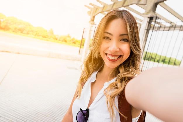セルフポートレートを取って笑顔の若い女性の肖像画