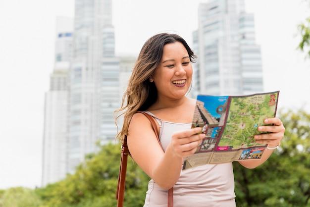 Портрет улыбающейся молодой женщины, смотрящей на карту города