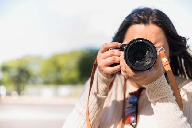 ぼかしの背景を持つ日中に写真を撮る女性