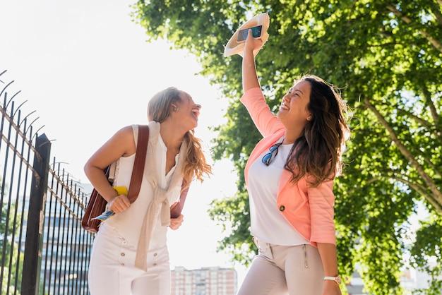 公園で踊っている彼女の友人を笑っている若い女性