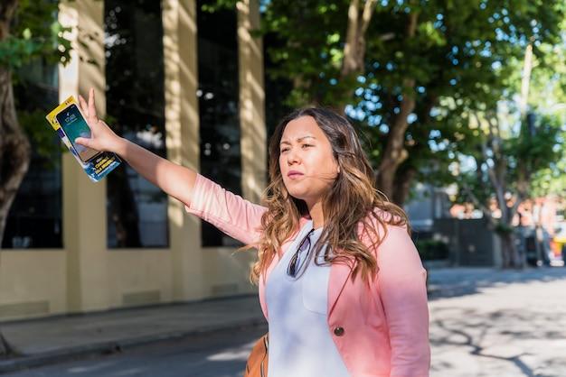 Женский турист, держа в руке сотовый телефон и карту, пытаясь поймать такси