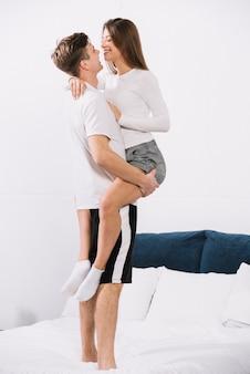 男はベッドの上の腕の中で女性を保持