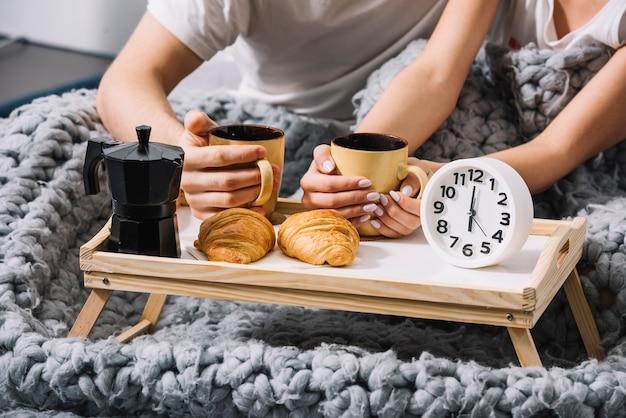 柔らかいベッドでコーヒーを飲むカップル