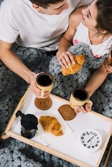 ベッドの中でコーヒーとクロワッサンを食べるカップル