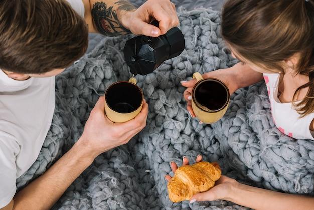 男はベッドの上のカップにコーヒーを注ぐ
