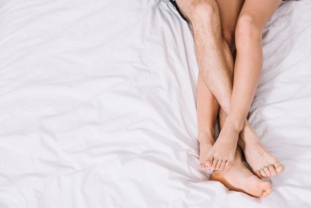 白いベッドで休む若いカップル