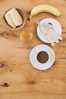パンの上から見た図。コーヒーカップ;ジャム;朝食のパンとバナナ
