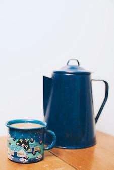 コーヒーのマグカップと白い背景に対して木製のテーブルの上のティーポットをぼかし