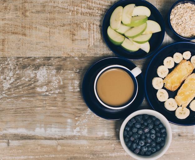 Синие ягоды; ломтик яблока; мюсли и хлеб с ломтиком банана на деревянный стол
