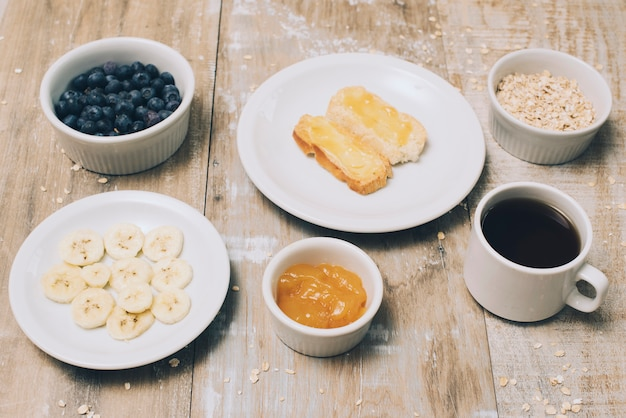 バナナのスライスジャム;ブルーベリー;オート麦と木製のテーブルの上のコーヒーカップ