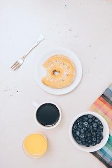 噛み付いていないドーナツ。ジュース;コーヒーカップと白い背景の上の青い果実