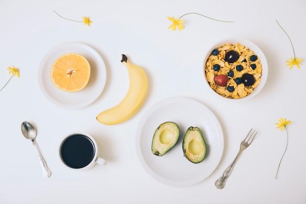 Злаковые хлопья; авокадо; банан; оранжевый пополам; кофе и цветы на белом фоне