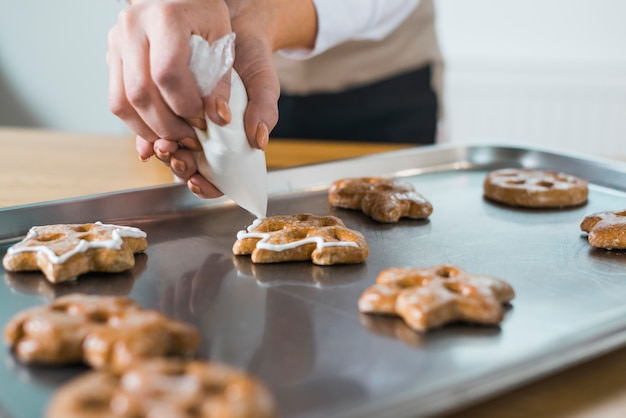 トレイにクリスマスの新鮮なクッキーにクリームを適用する女性