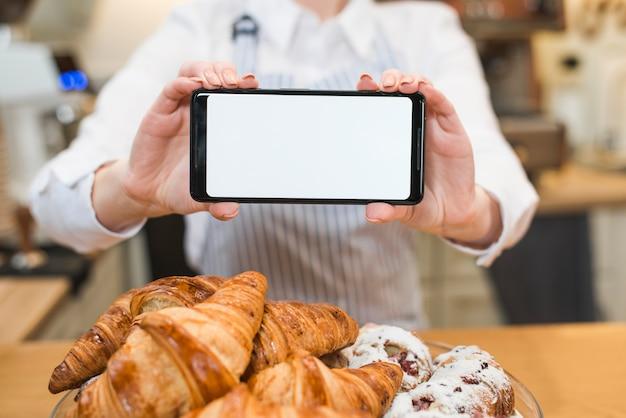 空白の白い画面を持つスマートフォンを保持している女性の前で新鮮なクロワッサン